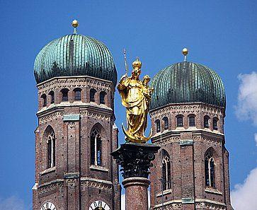La statua dorata di Santa Maria sulla sua colonna nella Marienplatz e le due torri di della Cattedrale di Monaco (Frauenkirche).