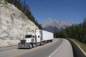 Un camion che sfreccia tra montagne rocciose.