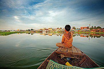 Ragazzo cambogiano a prua di una piccola imbarcazione affacciata sul lago.