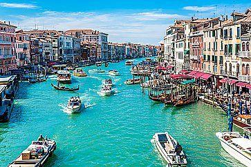 Vista di Canal Grande a Venezia, in una giornata di piena estate, con molte barche.