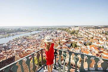 Una donna ammira il panorama della città di Coimbra al tarmonto.