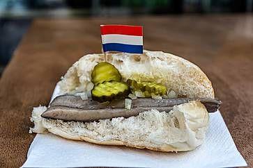 Broodje haring, spuntino tradizionale olandese, sandwich di pesce con aringhe, cipolle e cetrioli sottaceto.