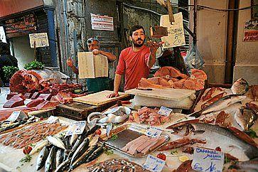 Un venditore in una bancarella piena di pesce fresco al mrcato del pesce di Palermo.