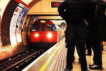 Piattaforma della metropolitana di Londra e treno in arrivo.