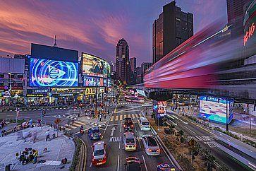 Vista notturna del trafficato quartiere di Bukit Bintang, con la sua stazione ferroviaria monorotaia circondata da grattacieli.