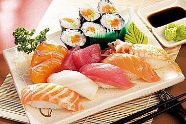 Sushi misto su un piatto in legno.