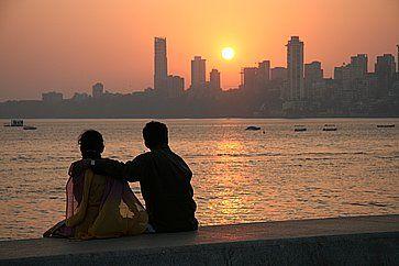 Una coppia ammira il tramonto a Chowpatty Beach (Mumbai).