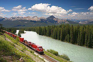 Treno merci lungo il fiume Bow nelle Montagne Rocciose Canadesi.