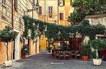 Vecchia via a Trastevere a Roma, con un piccolo ristorante.