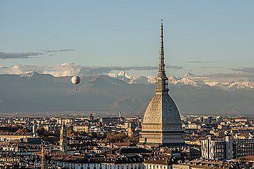 La vista di Torino al tramonto, in primo piano la Mole Antonelliana e sullo sfondo le cime innevate delle Alpi.