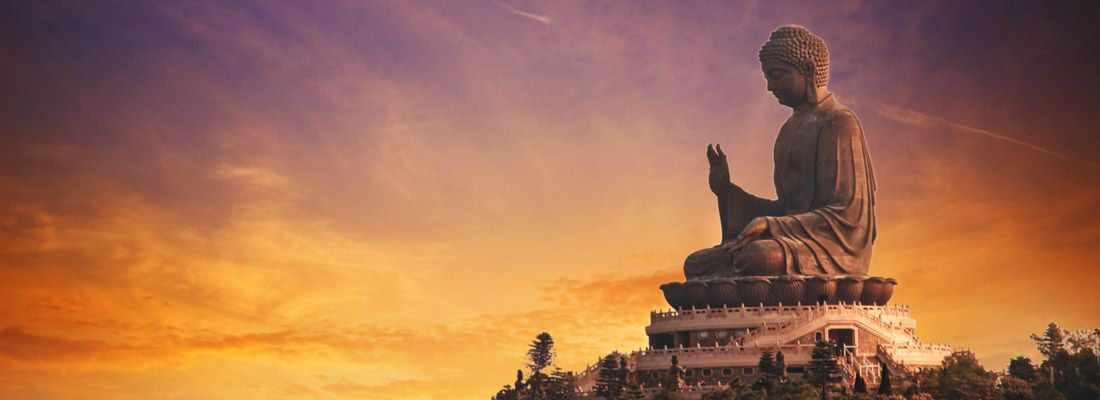 Il Buddha di Po Lin al tramonto, con un bellissimo cielo arancione e viola.