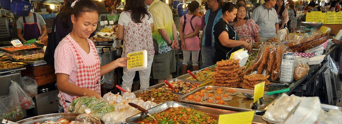 Una signora vende cibo al Chatuchak Market di Bangkok.