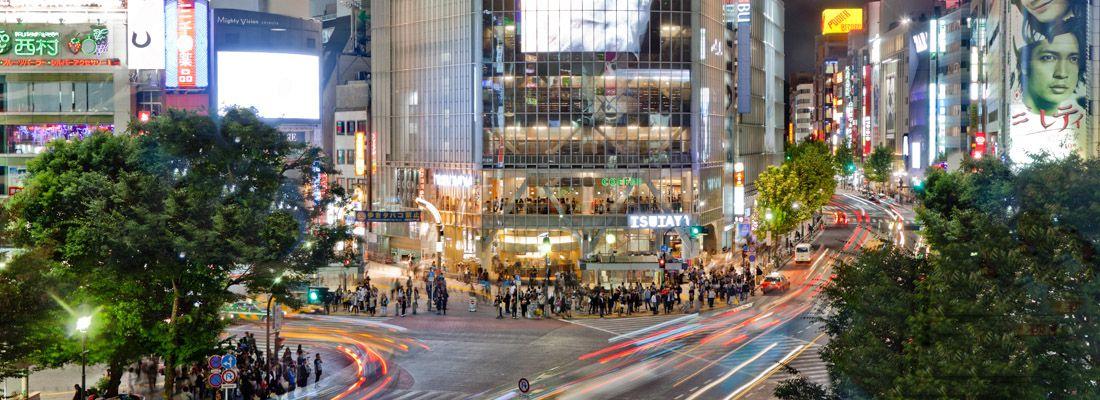 Persone attraversano il grande incrocio di Shibuya.