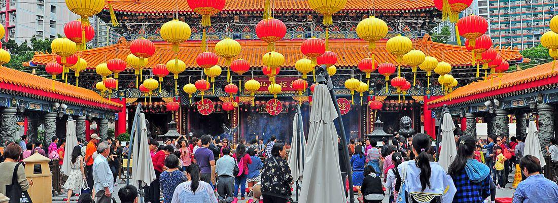Il tempio di Wong Tai Sin, con lanterne gialle e rosse, e molte persone durante una celebrazione.