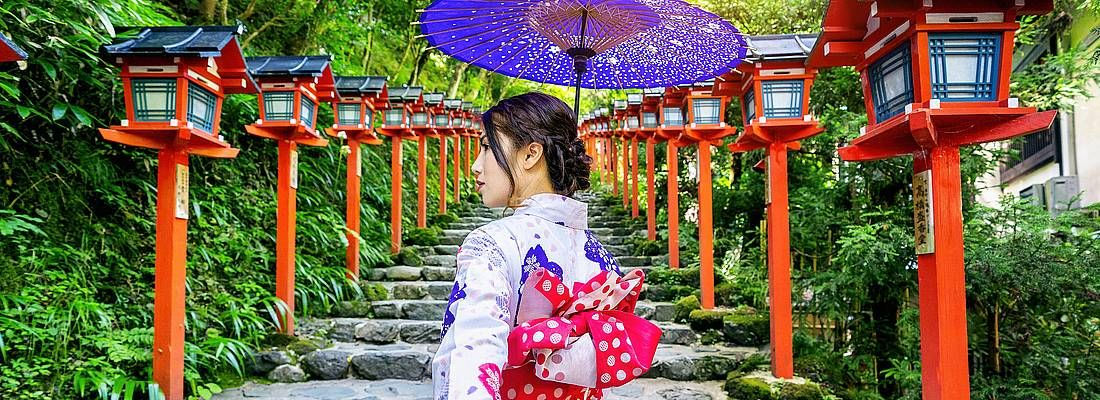 Donna in kimono tenuta per mano, in una zona tradizionale.