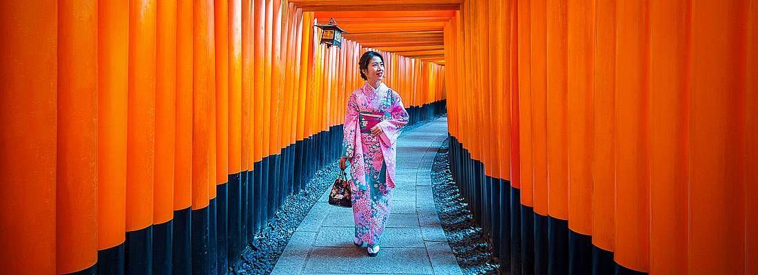 Una donna in kimono cammina tra i portali rossi del Fushimi Inari a Kyoto.