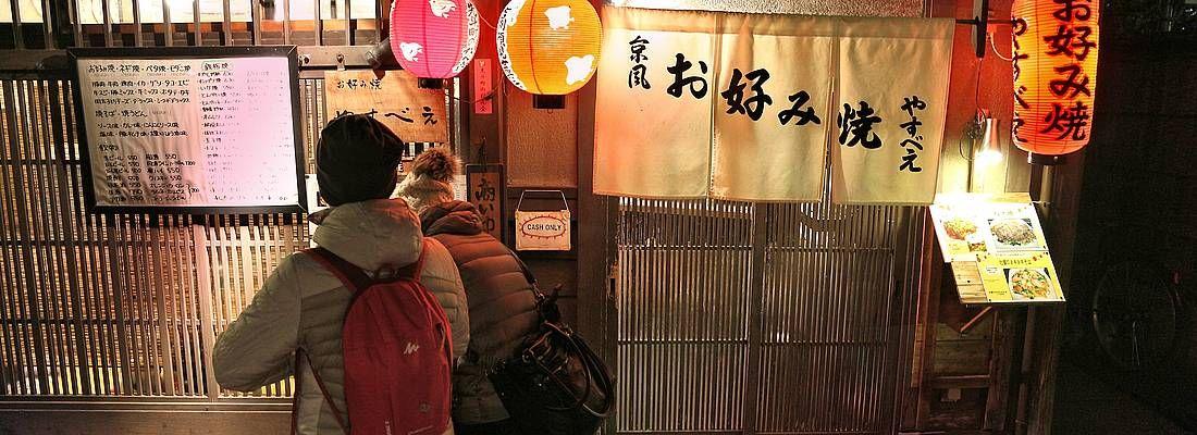 Persone all'ingresso di un ristorante tradizionale a Kyoto.