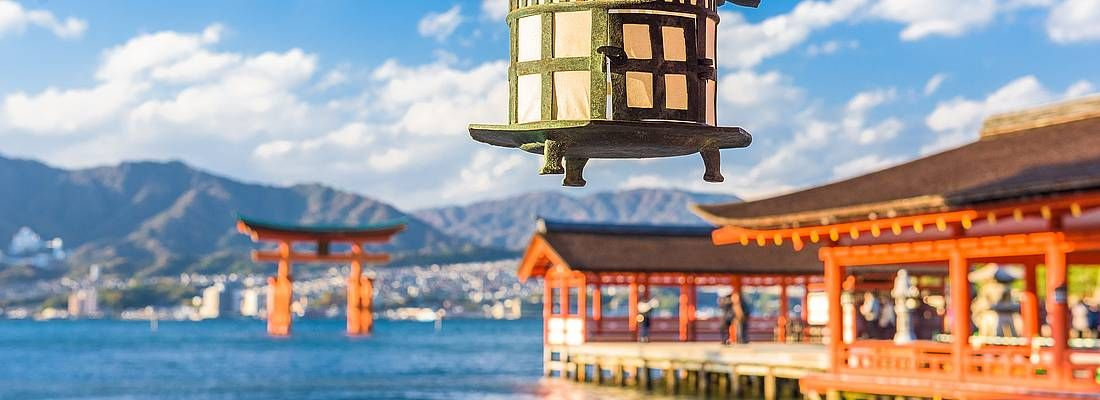 Lanterna al santuario Itsukushima e in lontananza il torii di Miyajima.