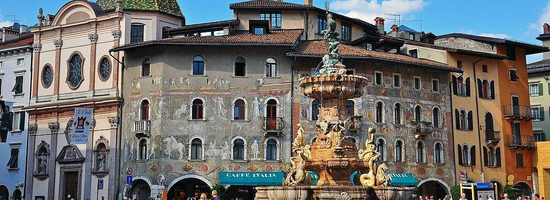 Piazza Duomo a Trento, la fontana in primo piano e dietro dei raffinati affreschi.