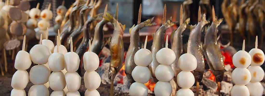Spiedini di pesce cucinati sulle braci in una bancarella Nikko.