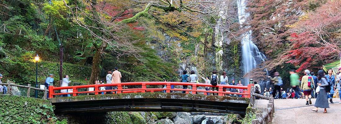 Ponte rosso al Parco Minoo, nei pressi di una cascata.