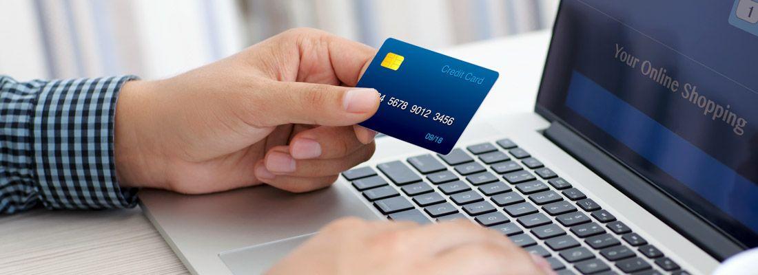 Una persona con una carta di credito in mano sta facendo acquisti online.