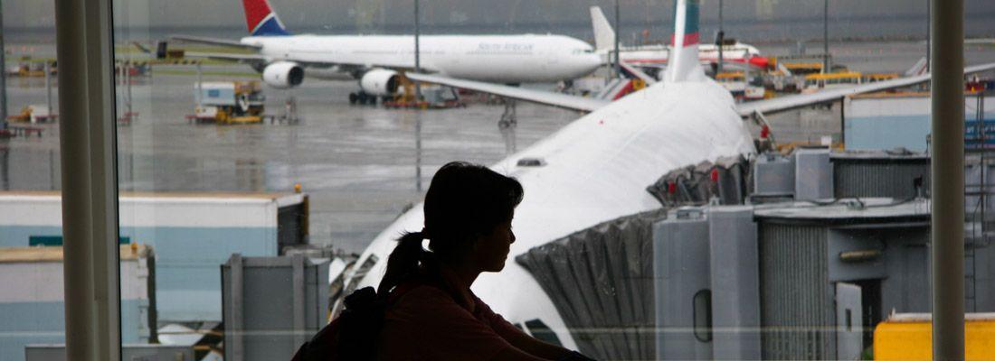 Silhouette di una ragazza in aeroporto, in attesa di imbarcarsi per un volo.