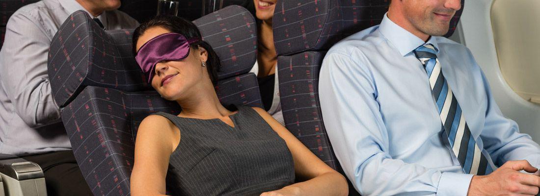 Una donna dorme in aereo, con una mascherina sul viso.