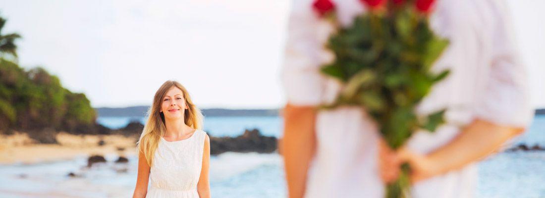 Un ragazzo in spiaggia, con delle rose dietro la schiena, fa una sorpresa ad una ragazza.