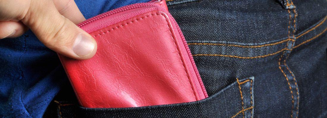 Una mano tenta di rubare un portafoglio, sfilandolo dalla tasca posteriore dei pantaloni.