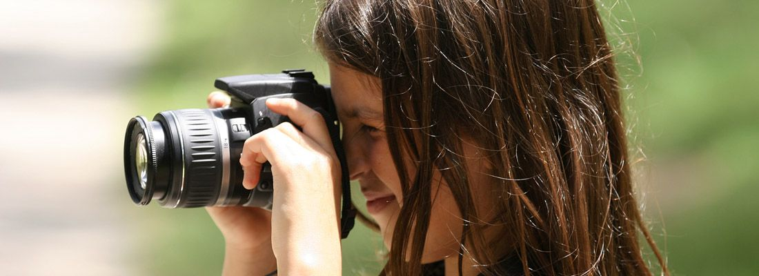 Una bambina fotografa usando una reflex digitale.