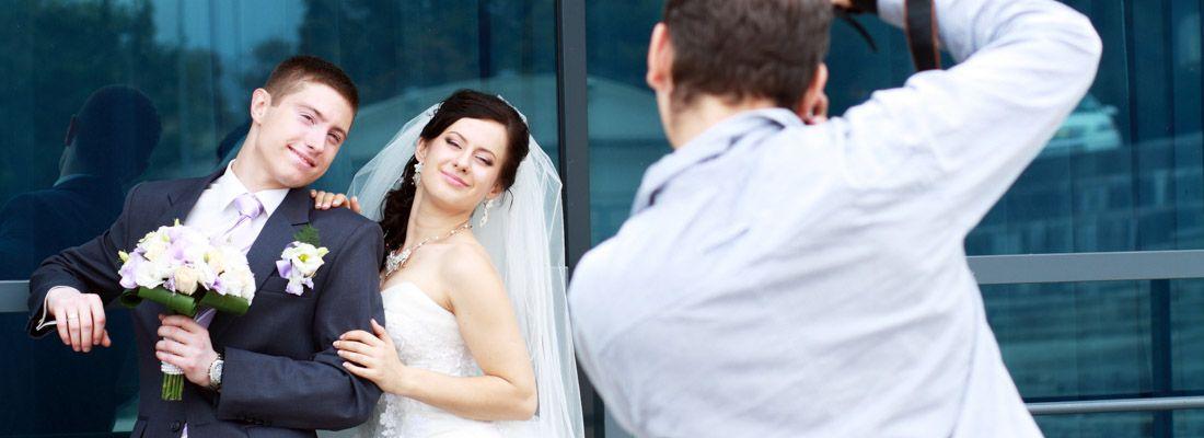 Un fotografo al lavoro mentre fotografa due sposi in posa.