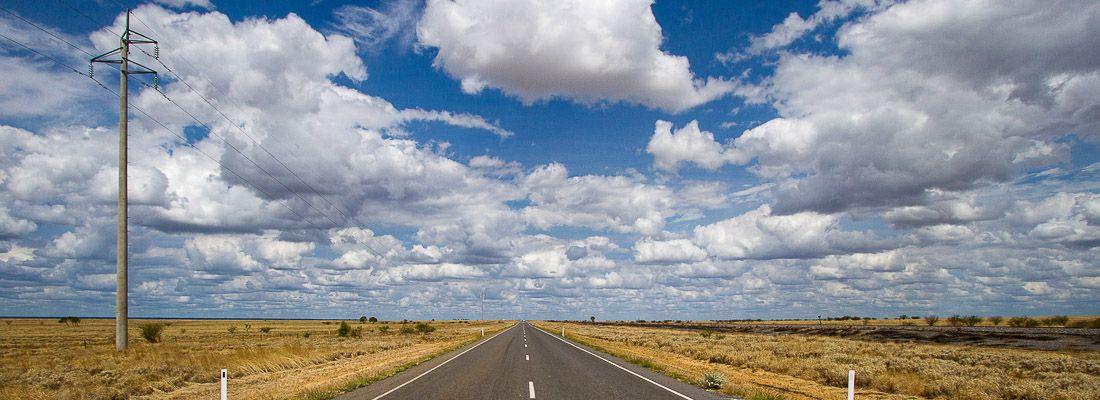 Strada deserta e diritta, con un cielo ricco di splendide nuvole.