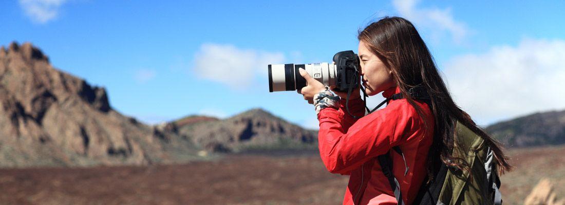 Una ragazza fotografa con un teleobiettivo durante un giro in montagna.