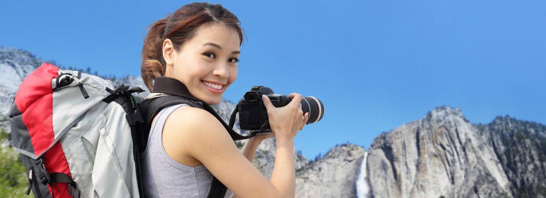 Ragazza fotografa una cascata in un parco naturale.