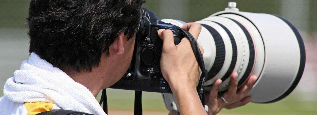 Un fotografo mentre usa un teleobiettivo.