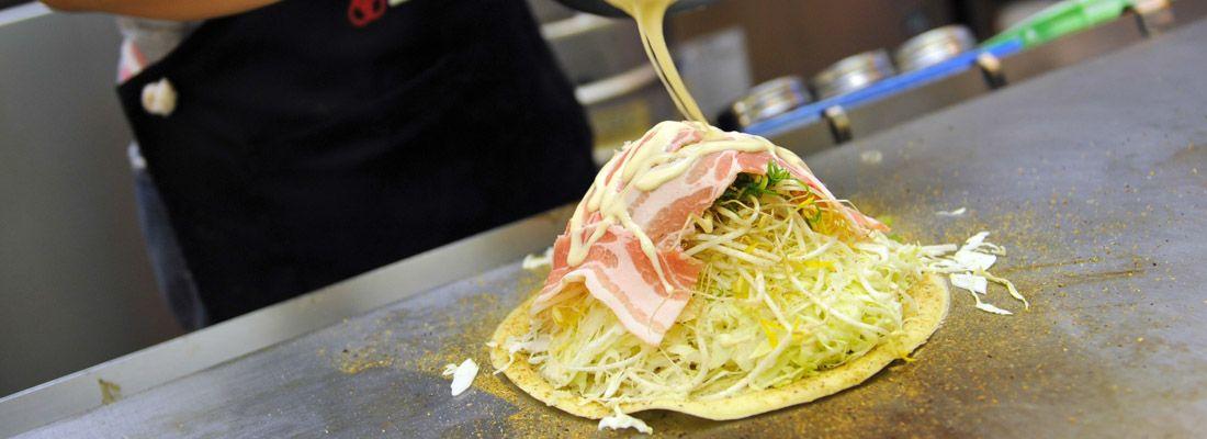 Una cameriera intenta nella preparazione di un okonomiyaki.