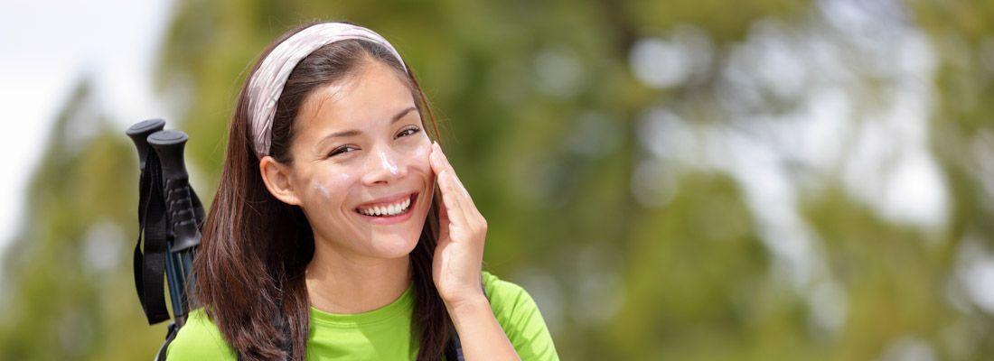Ragazza che fa trekking e si applica la crema da sole al viso.