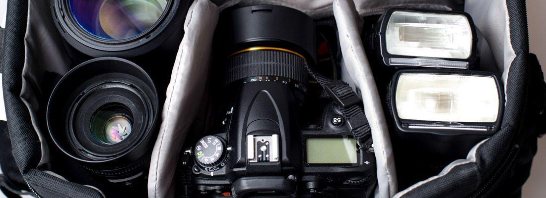 Interno dello zaino di un fotografo, con reflex, due obiettivi e due flash.
