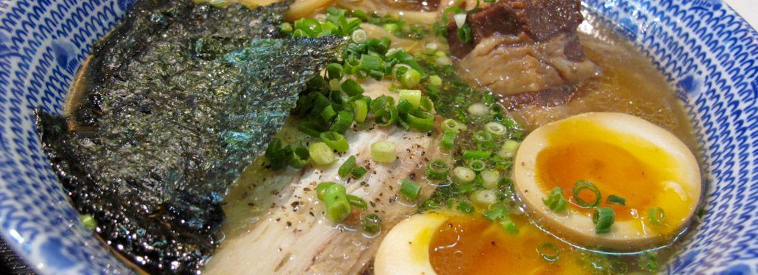 Ramen con brodo denso, pezzi di carne e uovo.