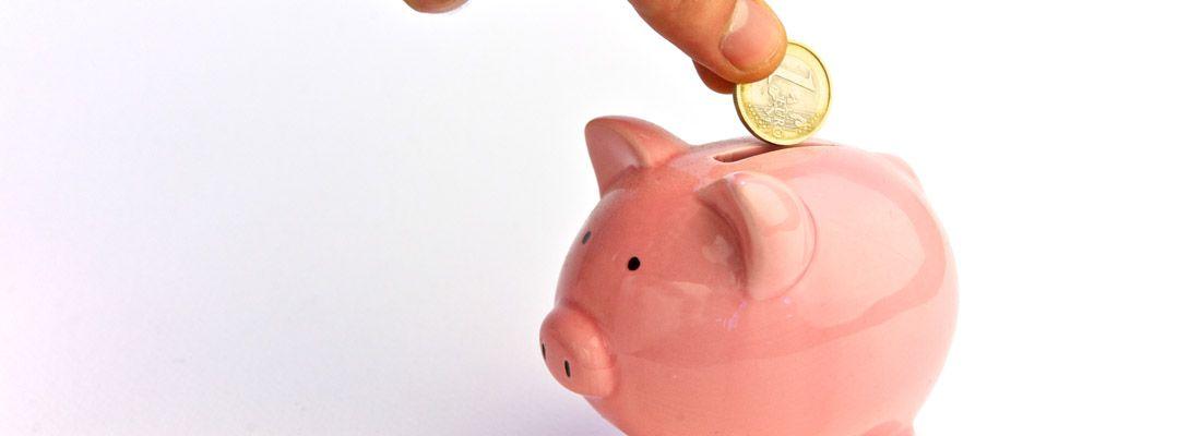 Una moneta viene messa in un maialino salvadanaio.