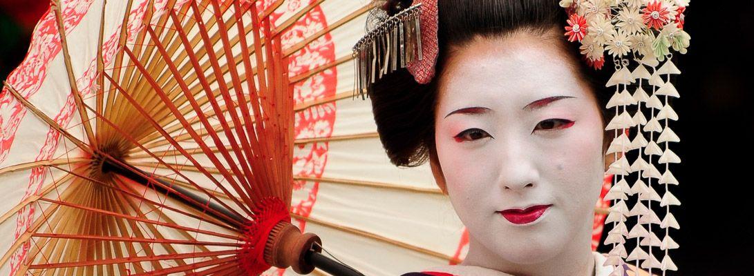 Una geisha con ombrello si mette in posa per una foto ricordo.