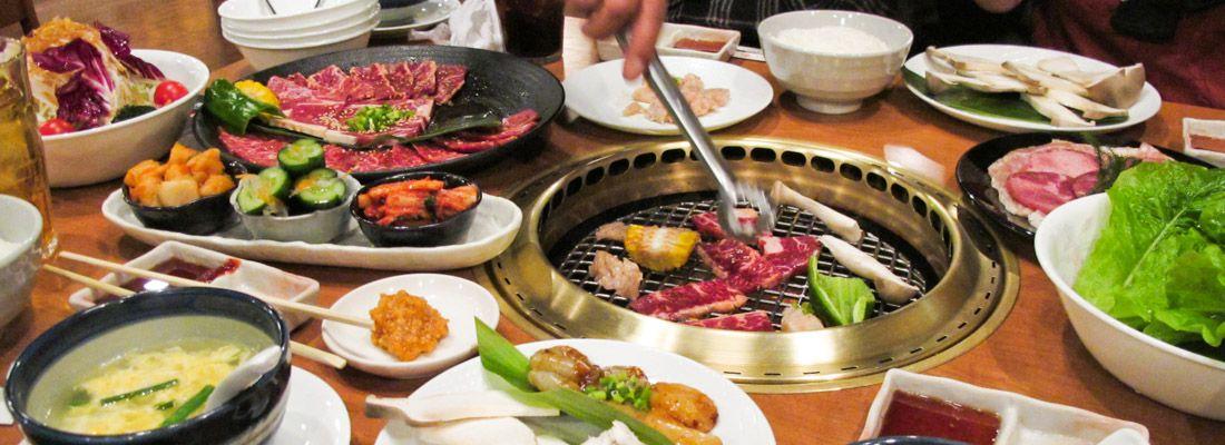 Tavolo imbandito e un commensale che prepara lo yakiniku, carne alla griglia.
