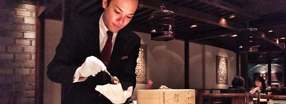 Cameriere cinese molto elegante prepara l'anatra alla cantonese al ristorante Hei Fung Terrace.