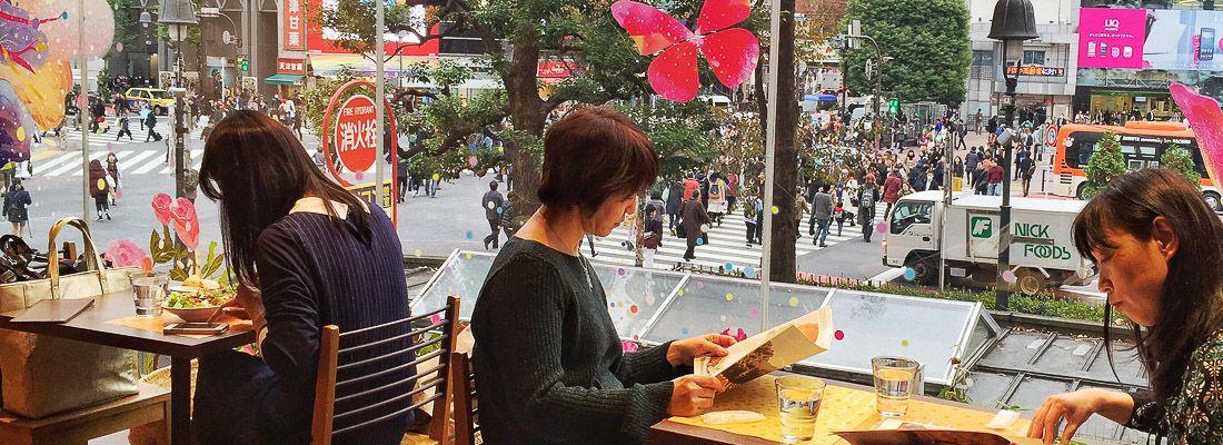 Persone sedute ai tavoli vicino alle finestre all'Occitane Cafe a Shibuya, sullo sfondo il famoso incrocio.