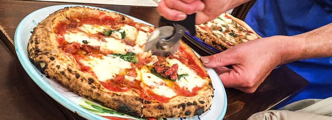 Un cameriere taglia una pizza margherita con un pizza cutter.