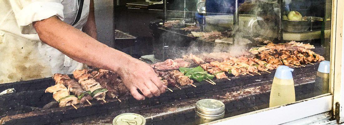 Uno chef intento nella preparazione di spiedini di pollo yakitori.