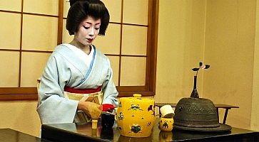 Donna in kimono prepara il tè in una stanza tradizionale.