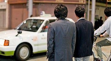Due salaryman attendono di attraversare la strada.