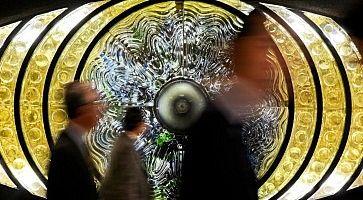 """Persone camminano davanti all'opera d'arte chiamata """"l'Occhio di Shinjuku""""."""